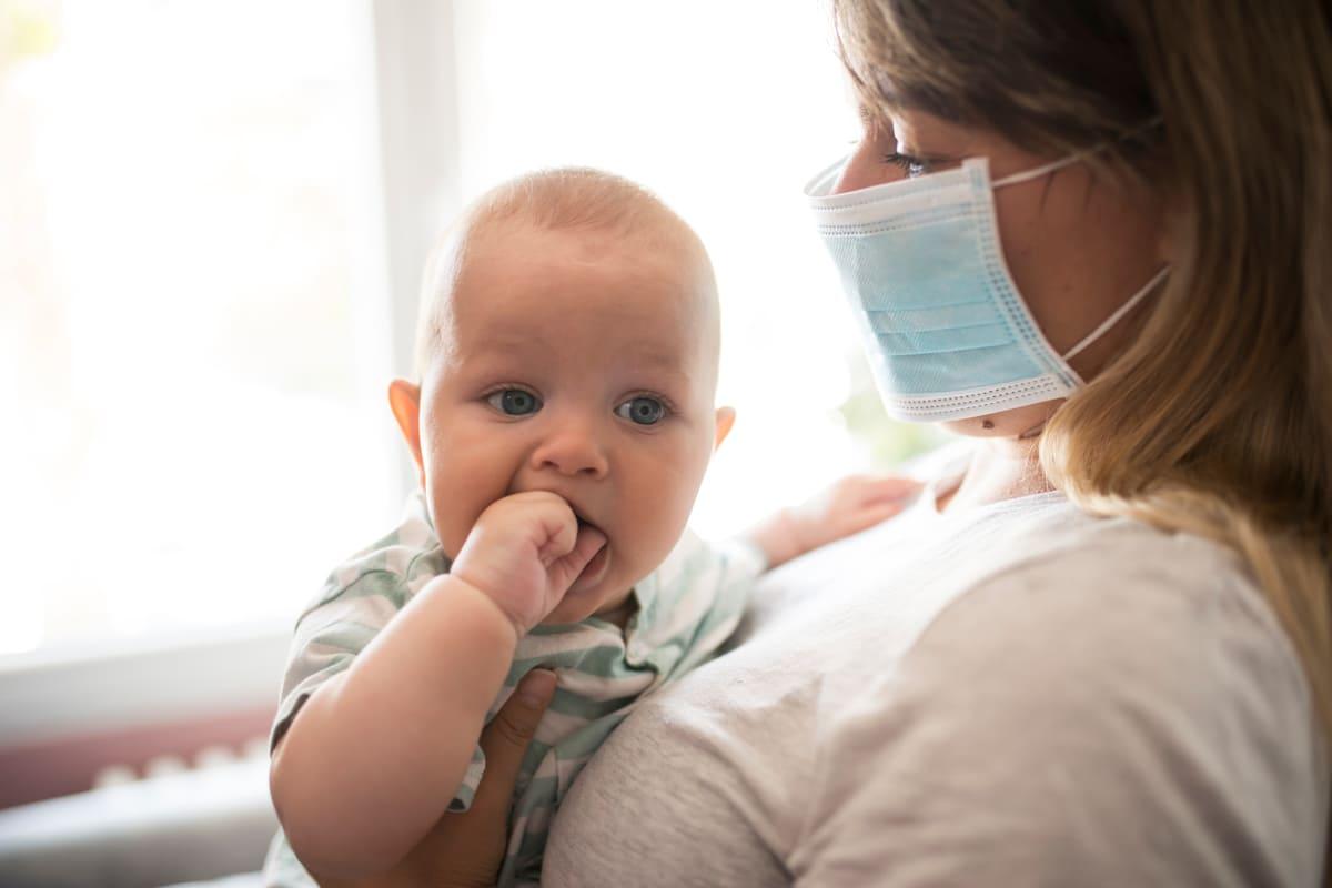 Mamma con mascherina e neonato in braccio