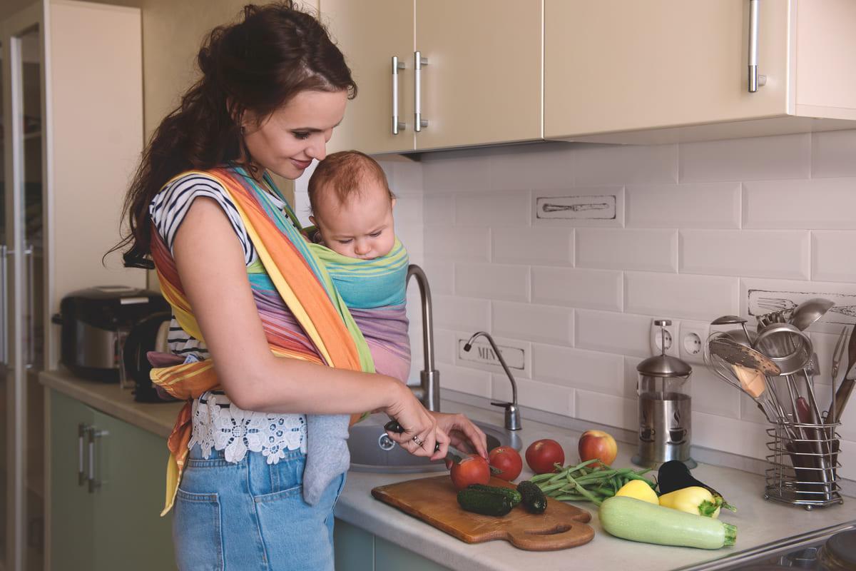 Mamma cucina con in braccio neonato
