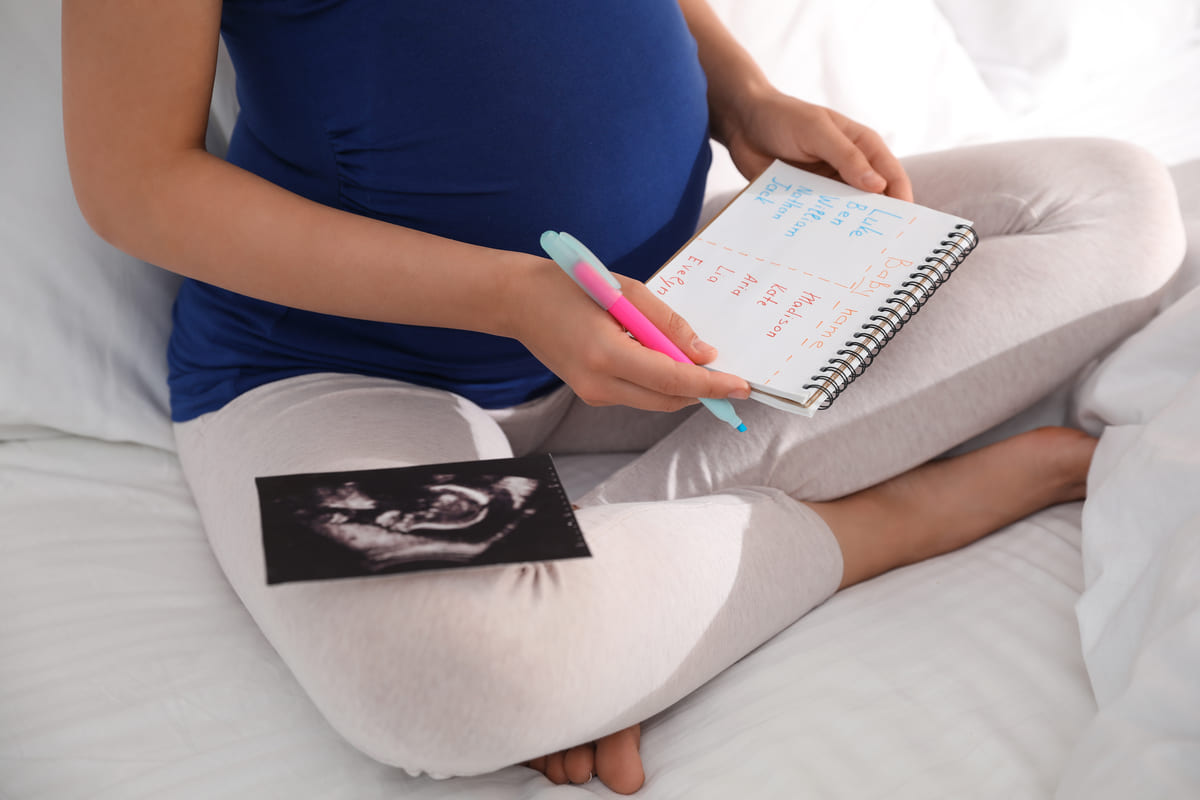 Donna incinta con lista di nomi di bambini
