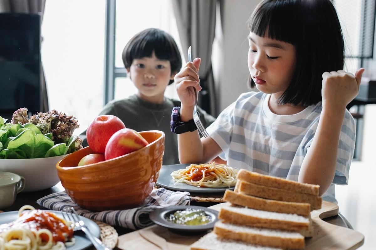 Bambini che mangiano pasta e pane