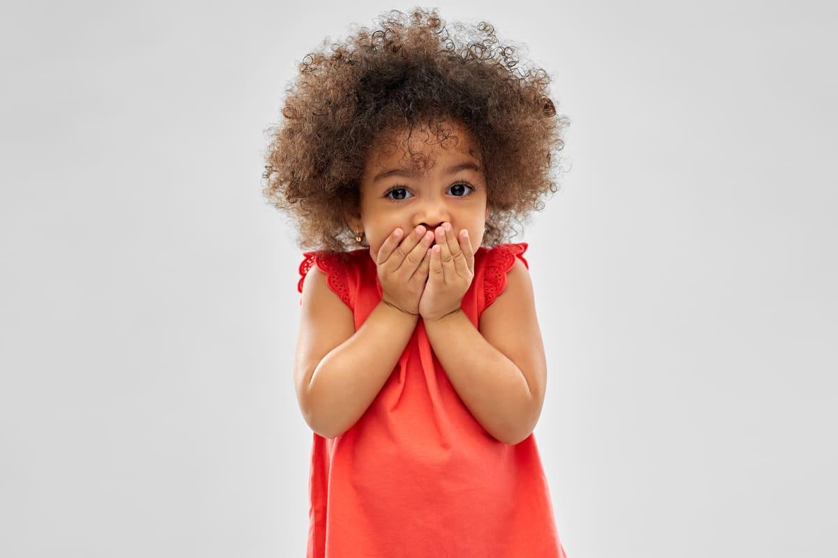 Bambina con le mani davanti alla bocca