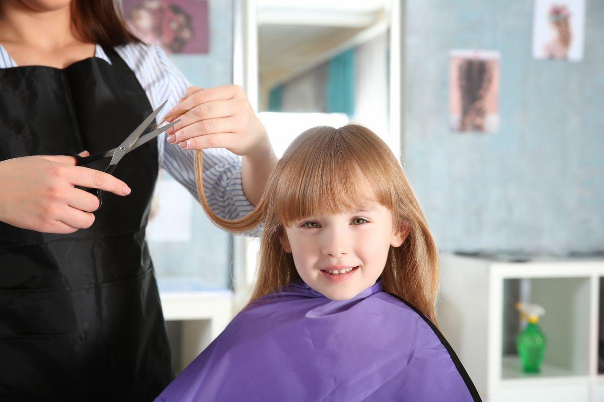 Bambina che taglia i capelli dalla parrucchiera