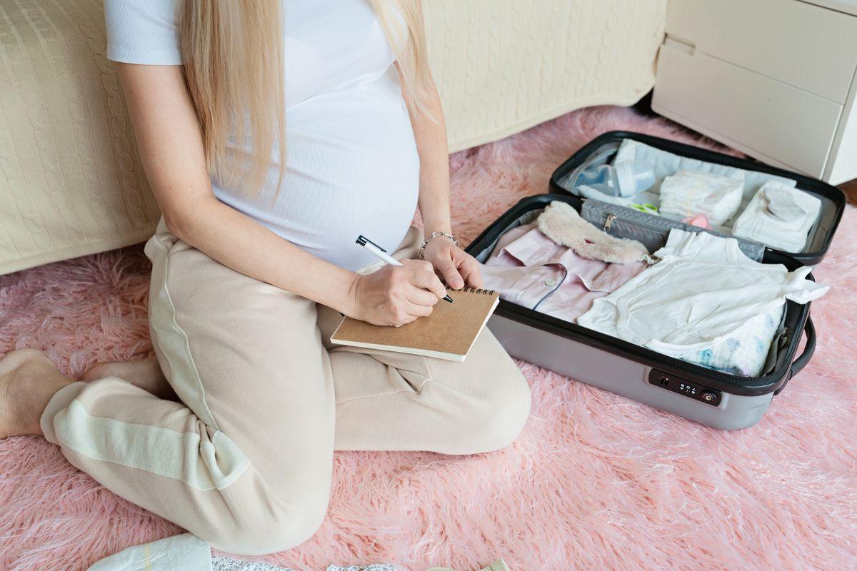 Donna incinta che prepara la valigia per il parto