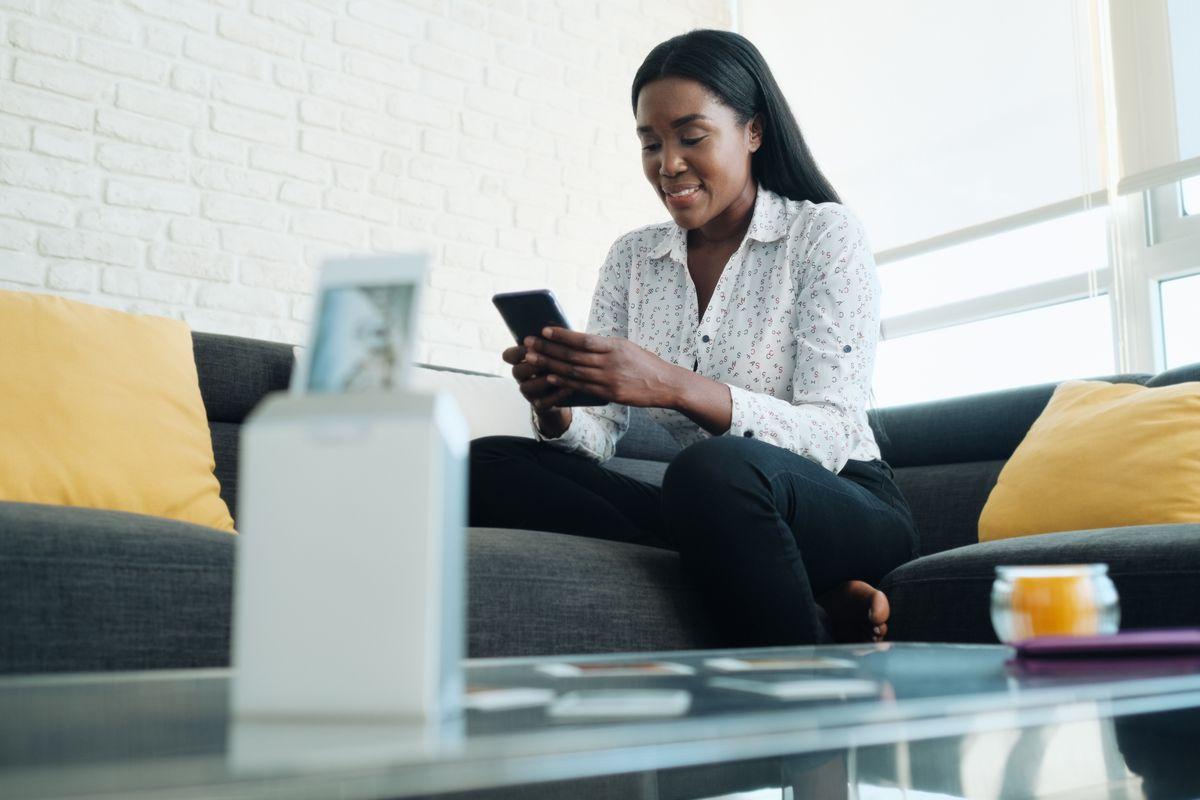 Donna che stampa una foto da smartphone con stampante portatile