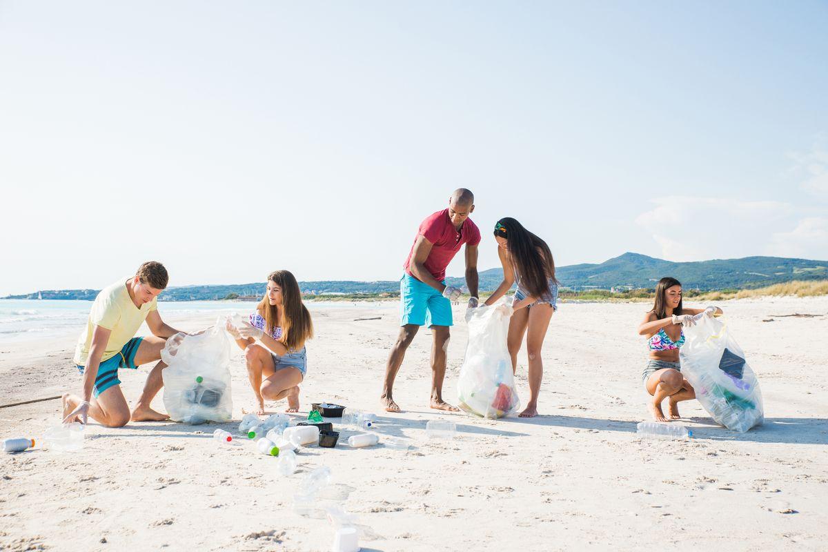 Ragazzi raccolgono rifiuti e plastica sulla spiaggia