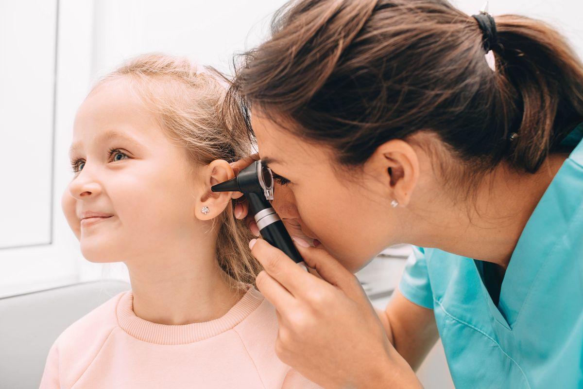 pediatra che visita bambina con otoscopio